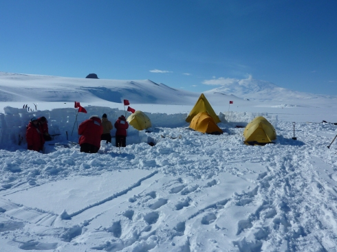 The snow school camp after setup, with people standing in the snow kitchen behind one of the snow walls.